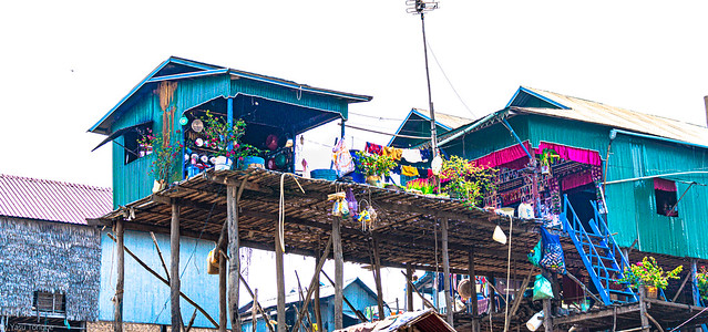 Beautifully decorated house in the floating village of Kampong Khluk with plants and architectural trim and it looks like a cooking utensil shop in the front, Cambodia.   789a