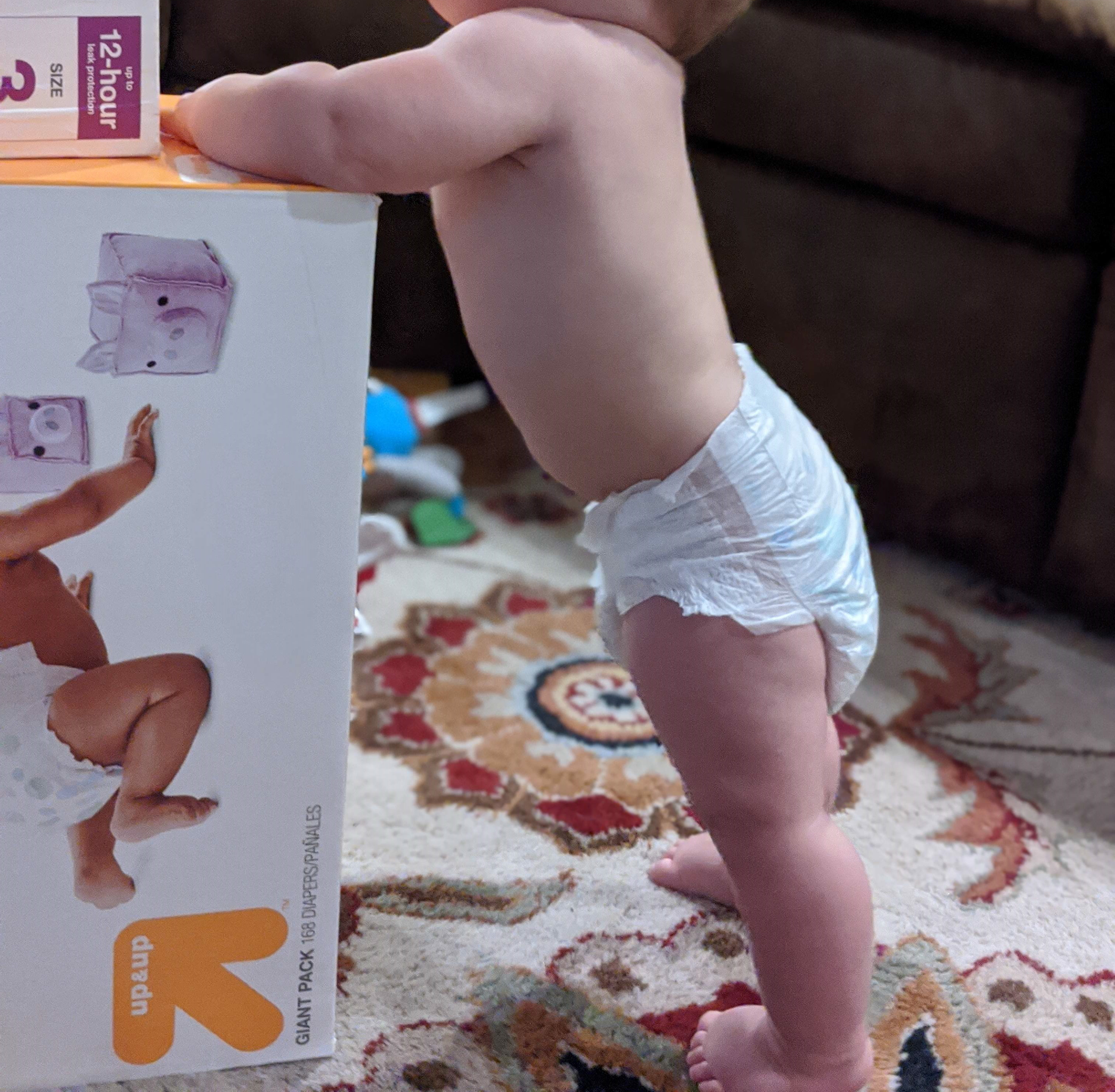 Baby in a diaper next to a box of diapers