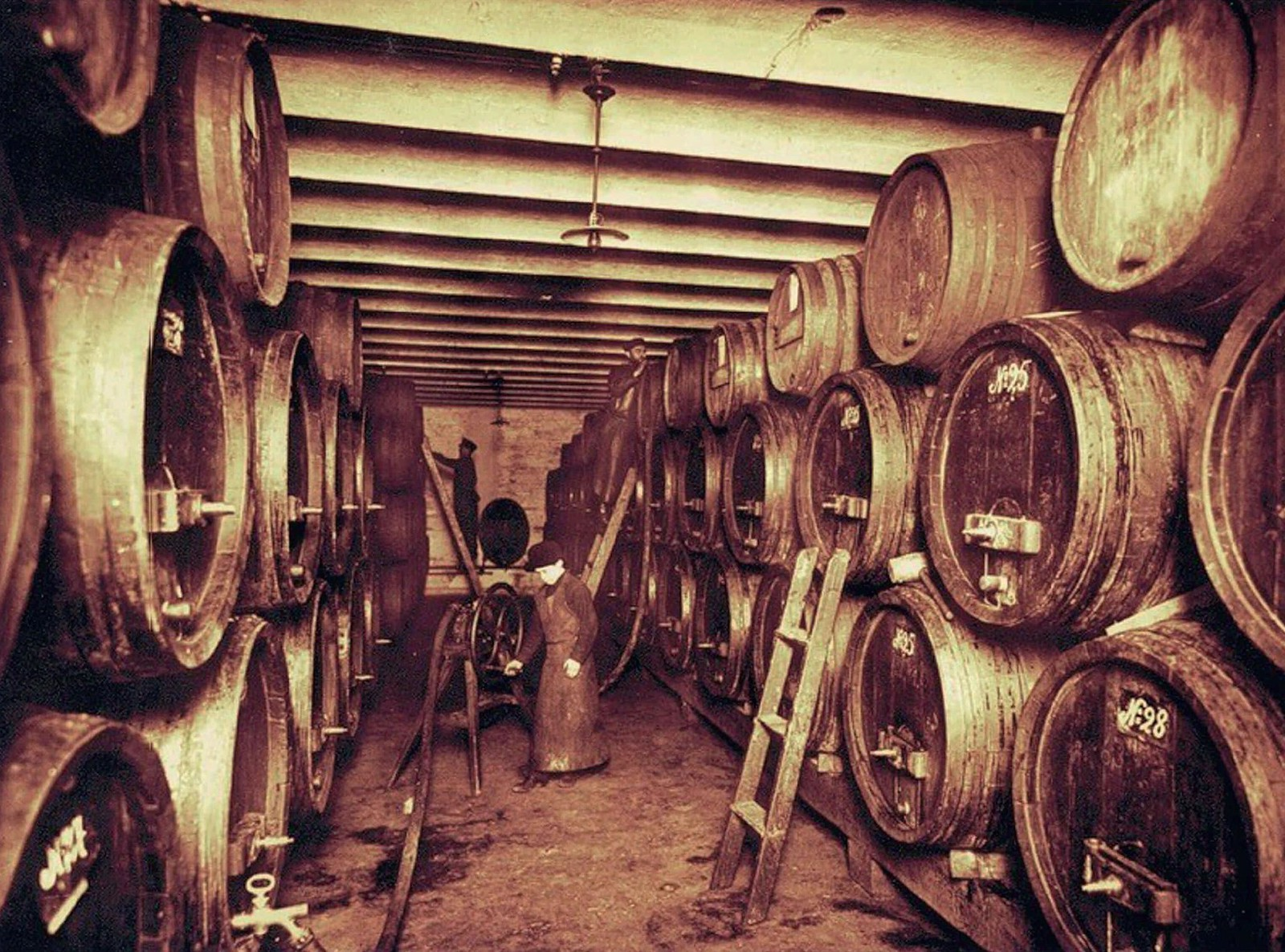 98. 1901. Рабочий торгового дома братьев Шталь за перекачкой вина на складе