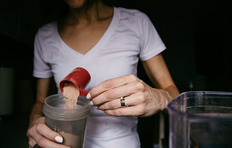 Woman making a protein shake with powder