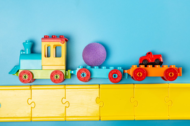 Children's plastic constructor steam locomotive with toys and road on blue background