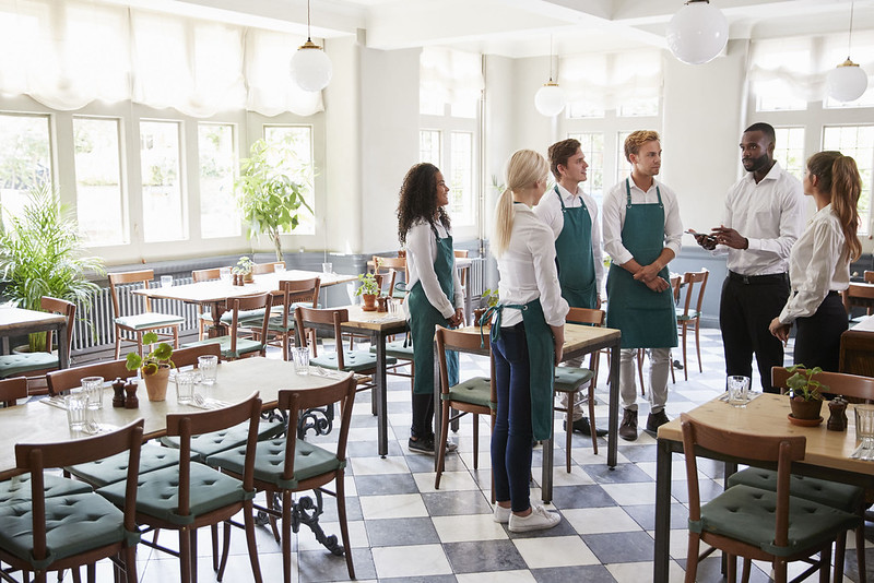 Staff Attending Team Meeting In Empty Dining Room