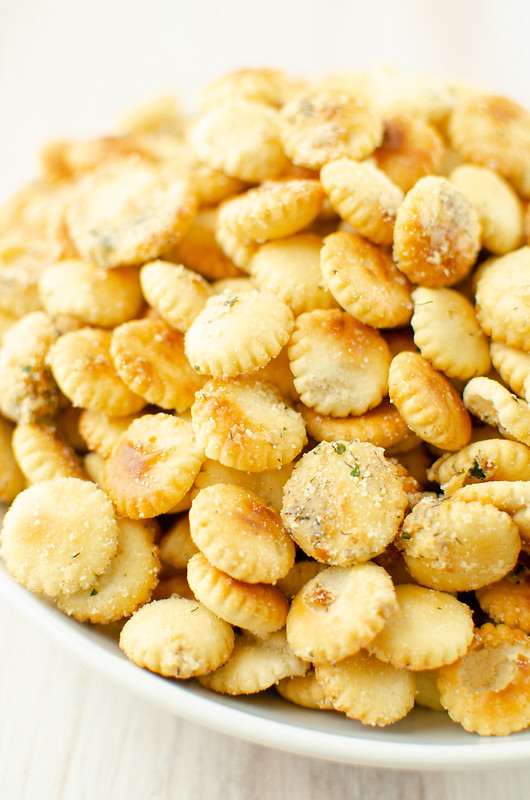 White bowl full of oyster crackers coated in ranch seasoning dried dill, and Parmesan cheese