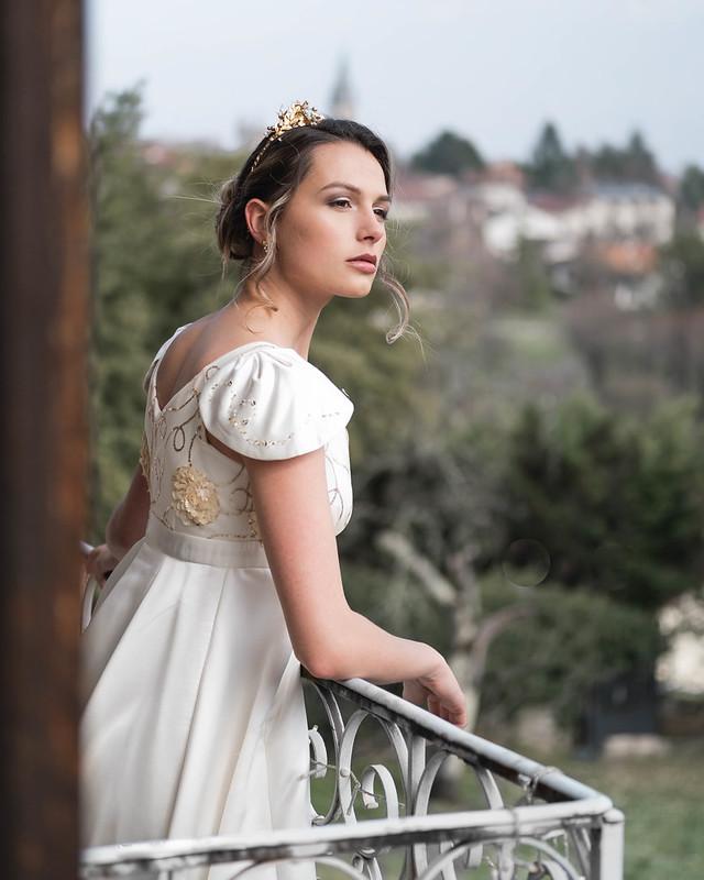 Amandine, se penchant au balcon, en robe de satin ivoire perle de doré, avec un diadème doré sur la tête