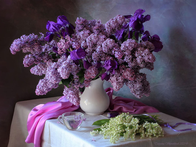 With a bouquet of lilacs and lilies of the valley