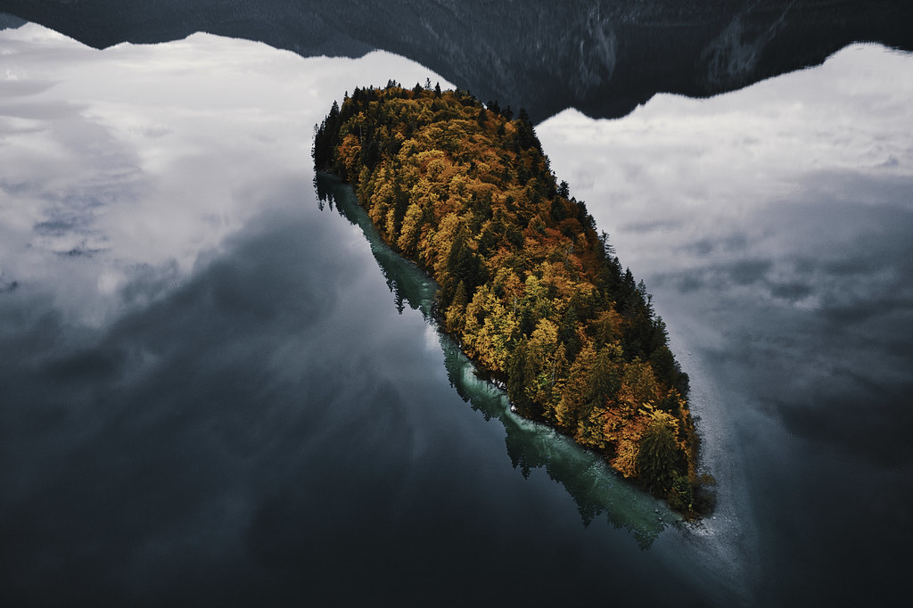 a view of an island in a lake with mountains in the reflection,