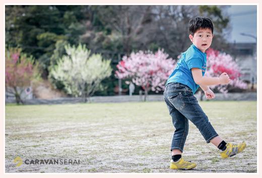 愛知県森林公園のハナモモをバックにボール遊びをする少年