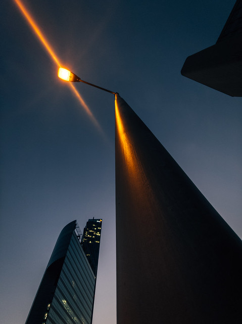 Close-up of a street lamp in the evening. Skyscraper in the background