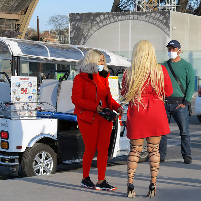 Blond women negotiating a ride on TukTuk.