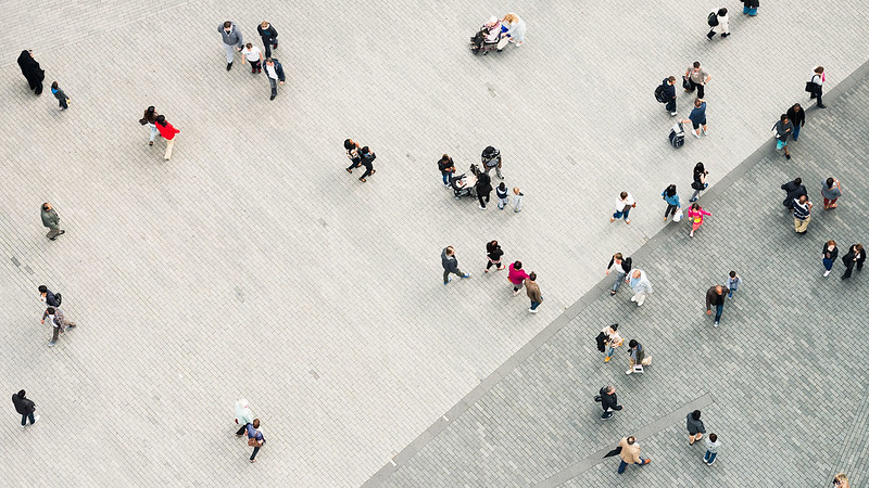 An aerial photo of groups of people walking down a paved area