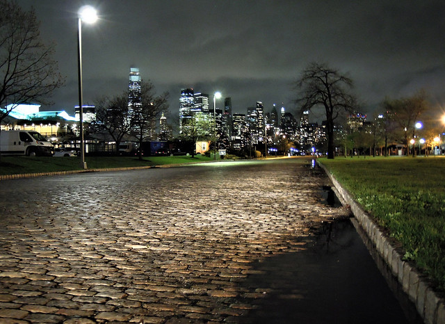 Lower Manhattan from Liberty State Park around 11 pm. I was the only person there. The cobblestones of Johnston Avenue/Audrey Zapp Drive were lit by my car's headlights as the shot was taken in absolute silence. Jersey City. April 15 2021