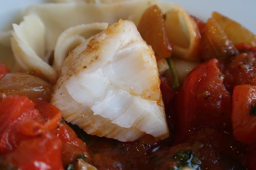 Nahaufnahme eines halbierten Fischstückes auf Tomaten-Paprika-Pfannengemüse und Bandnudeln