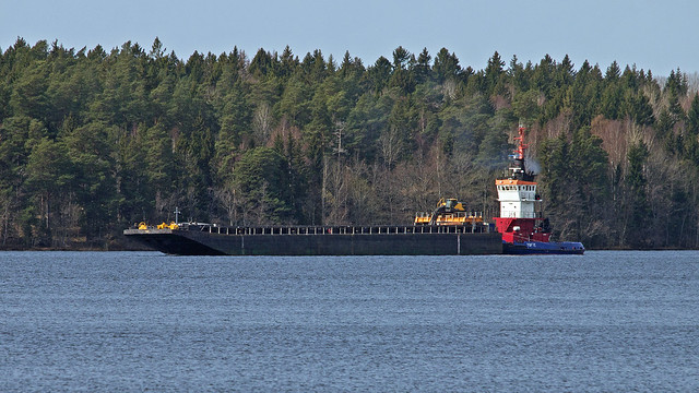 The pusher tug Tofte pushing a barge in Lake Mälaren, in the background Färingsö island