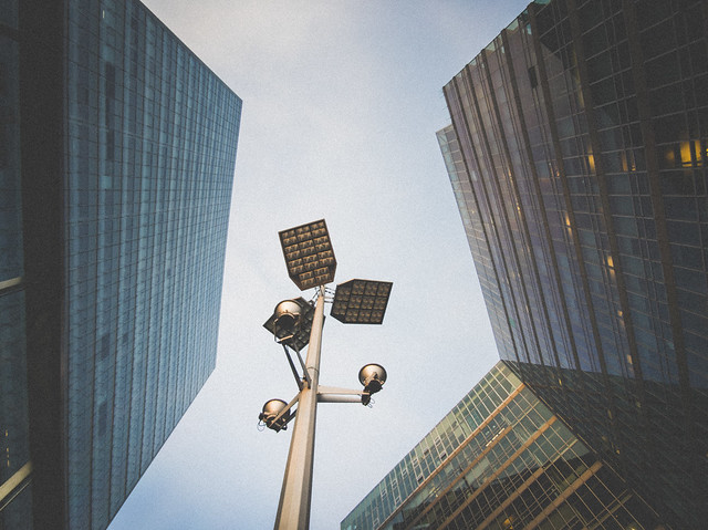 Pedestrian's view of the skyscrapers in the city. Street lamp between the high-rises