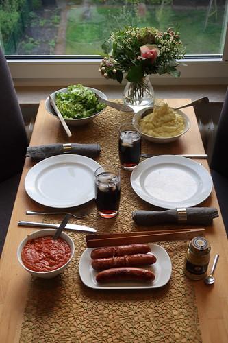 Krakauer mit Currysoße, Kartoffelstampf und Eichblattsalat (Tischbild)