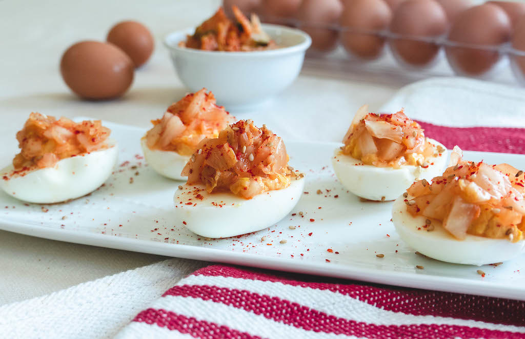 A plate of deviled eggs topped with kimchi.