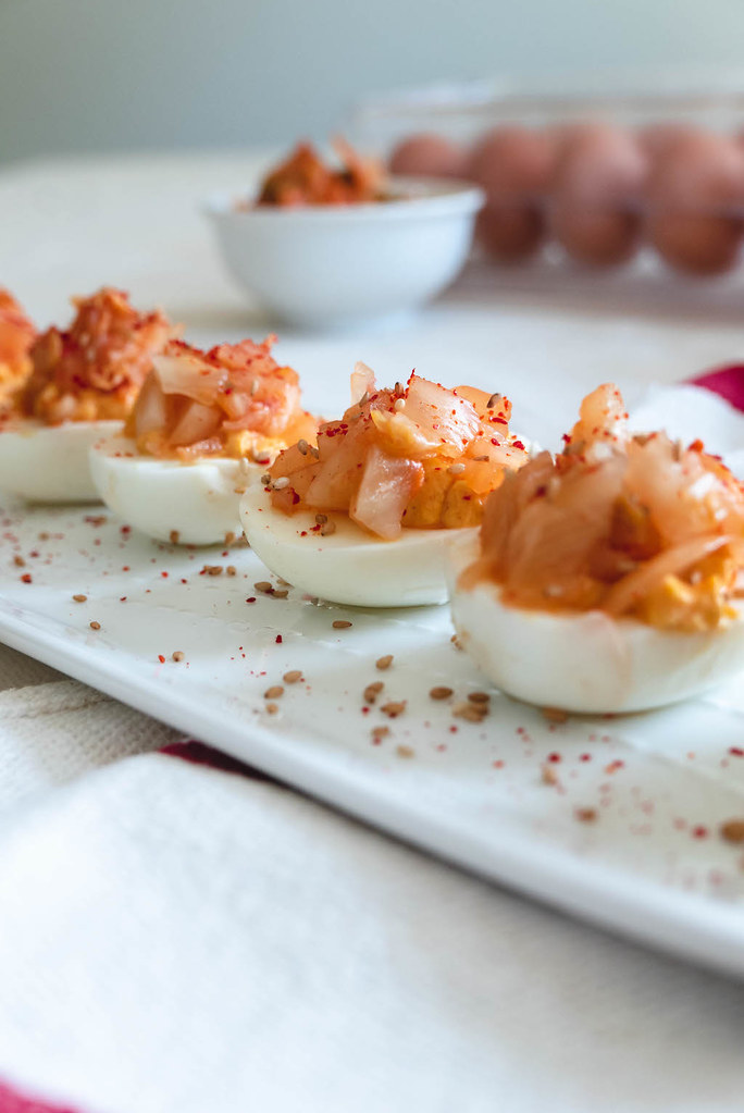 Kimchi deviled eggs lined up on a tray.