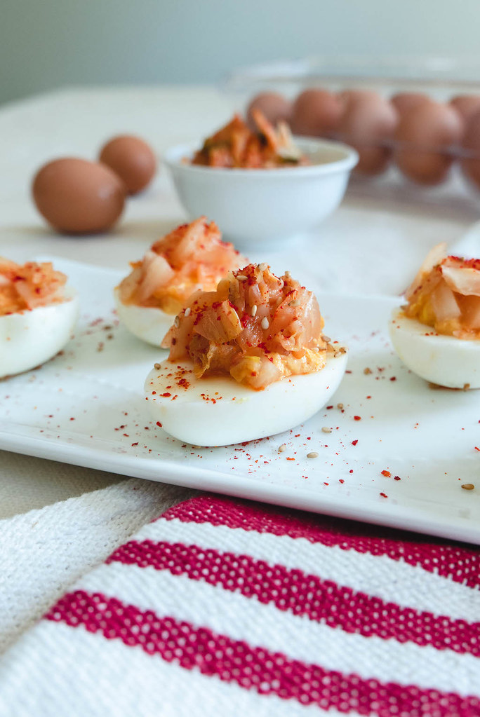 A plate of deviled eggs. Kimchi and eggs sit in the background.