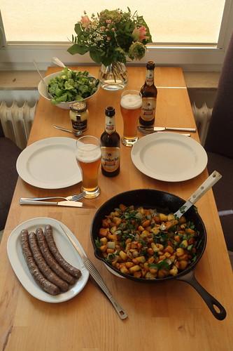 Frische Rinderbratwurst zu Bratkartoffeln und Eichblattsalat (Tischbild)