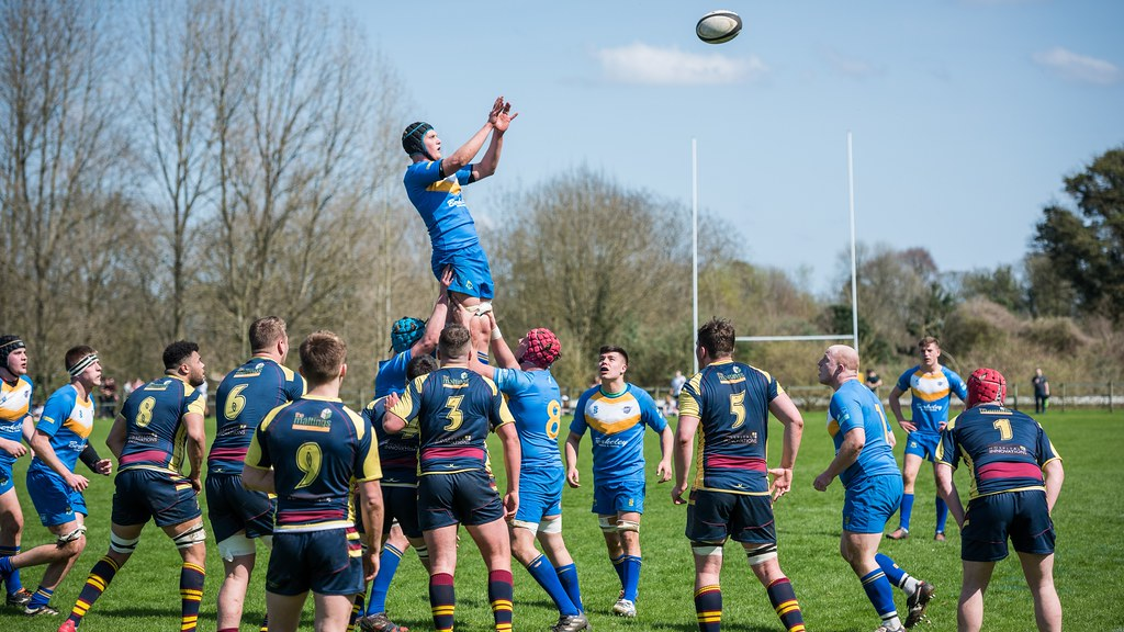 A rugby player jumps to catch the ball watched on by other players