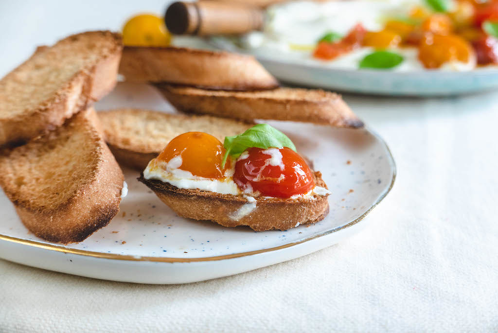 A plate of toasted bread. One bread is topped with whipped feta and tomato.