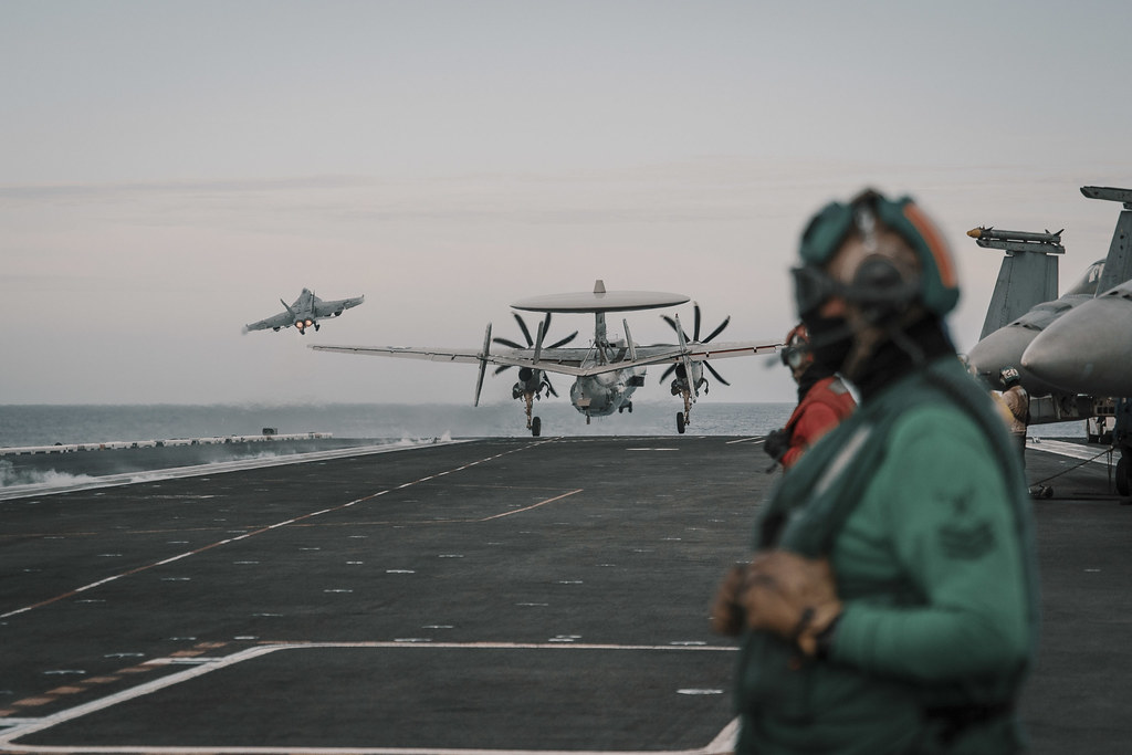 "An F/A-18E Super Hornet, assigned to the ""Tomcatters"" of VFA 31, left, and an E-2C Hawkeye, assigned to the ""Liberty Bells"" of VAW 115, launch from the flight deck of USS Theodore Roosevelt (CVN 71)."