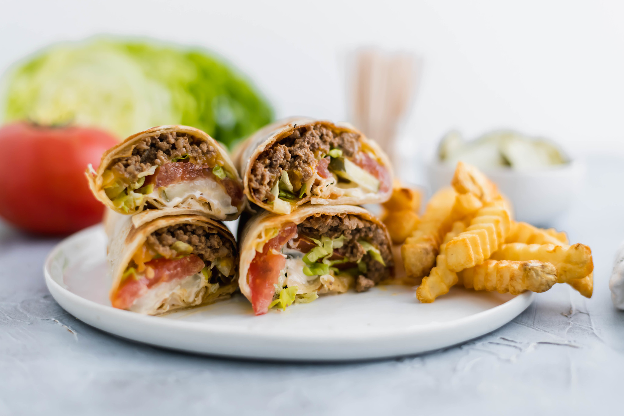A fun twist on the classic cheeseburger, these Cheeseburger Wraps feature ground beef, cheese, burger sauce, lettuce, tomato and pickles all wrapped up in a flour tortilla.