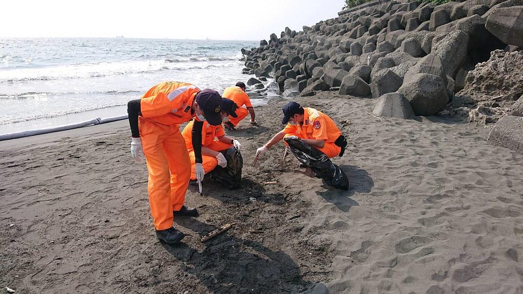 海巡協助清除沙灘油污塊。