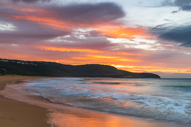 Sunrise at the seaside with pastel coloured clouds