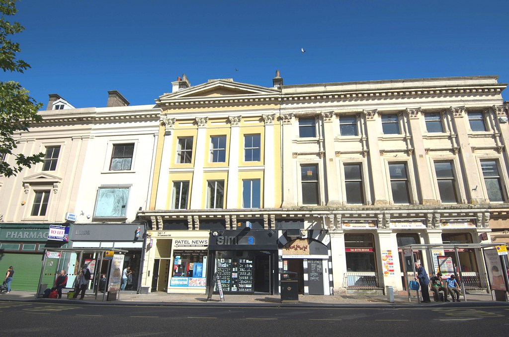 Ornate Georgian building with tacky shop fronts in Preston