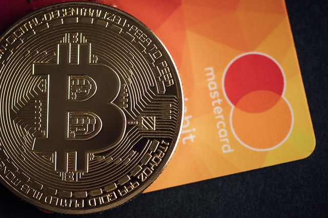 Close-up of a Bitcoin physical coin on a Mastercard credit card