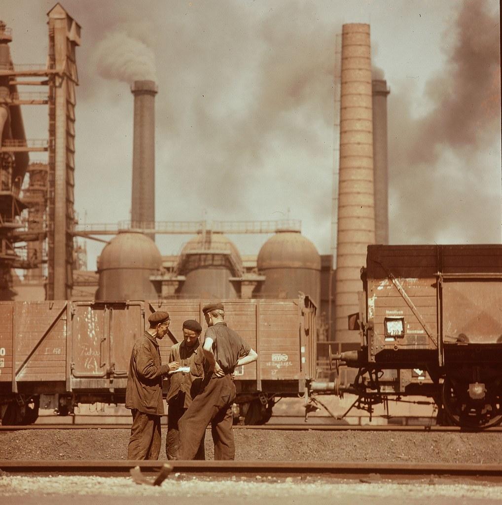 28. Трое сталелитейщиков на железнодорожных путях перед дымовыми трубами комбината в Дунауйварош