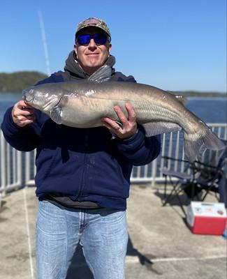Photo of man holding large blue catfish