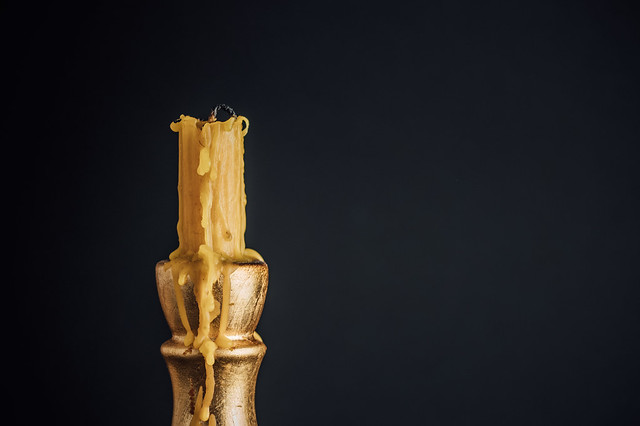 Close-up of an unlit candle with a candle holder covered with wax