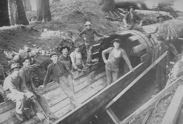 Workers constructing wood stave pipeline, 1900