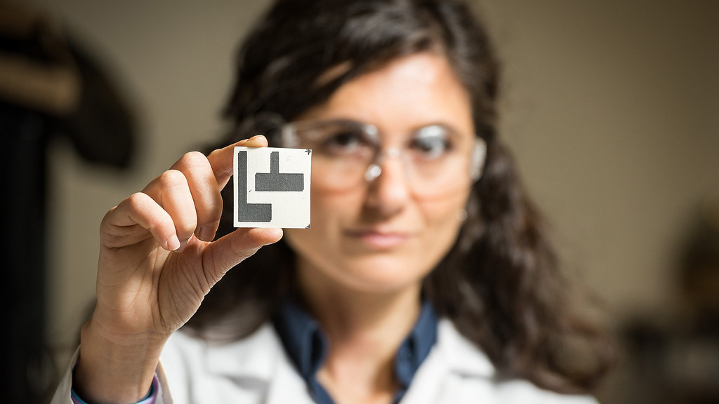 An academic holds up a biofuel cell.