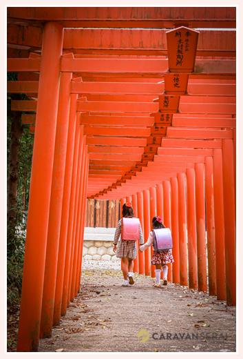 神社の赤い鳥居の下を歩く小学生姉妹 ランドセル