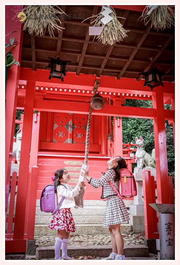 神社で鈴を鳴らす小学生の姉妹 ランドセル