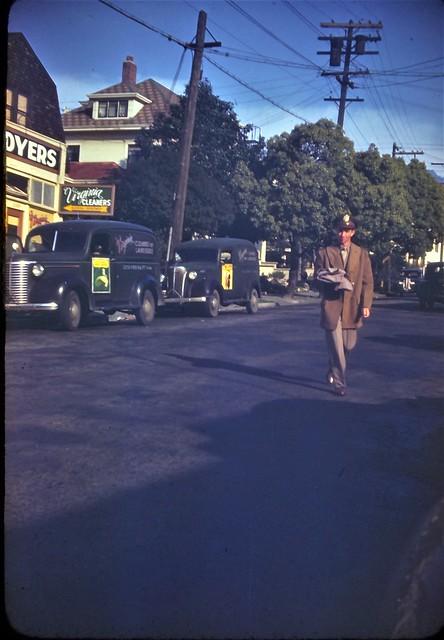 1940's Kodachrome slide showing a serviceman walking down a street in uniform. Likely taken during WWII.