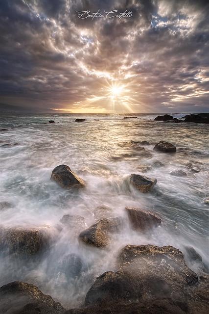 The sea creates traces of light on a rock canvas