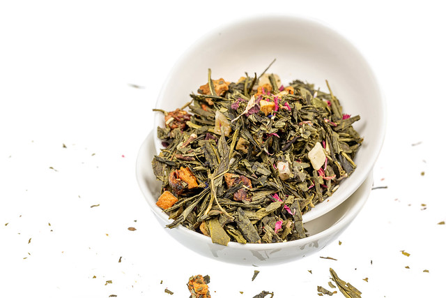Dried green tea leaves with citrus slices, dried fruits and petals