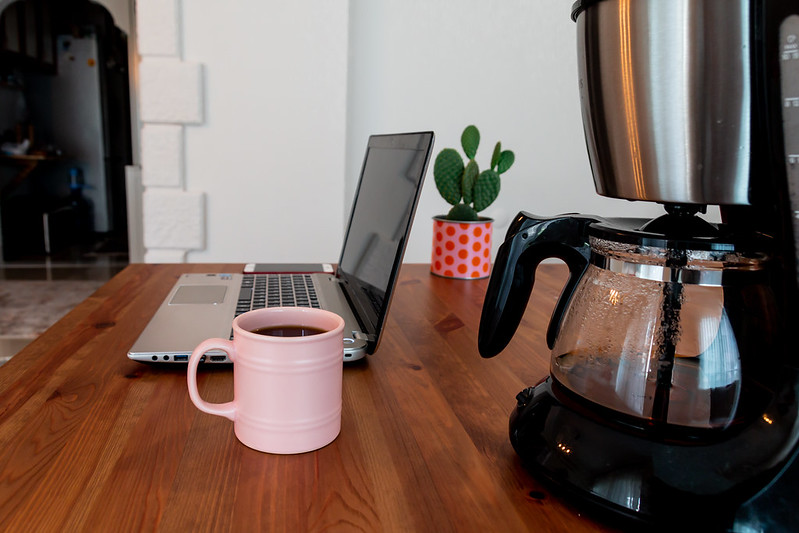 Filter coffee machine on a desk with pink cup and laptop