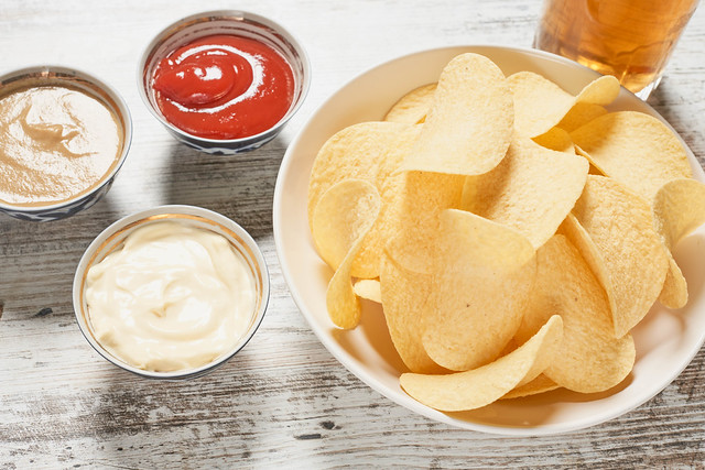 Bowl of crispy potato chips, sauces and glass of beer on the wooden table
