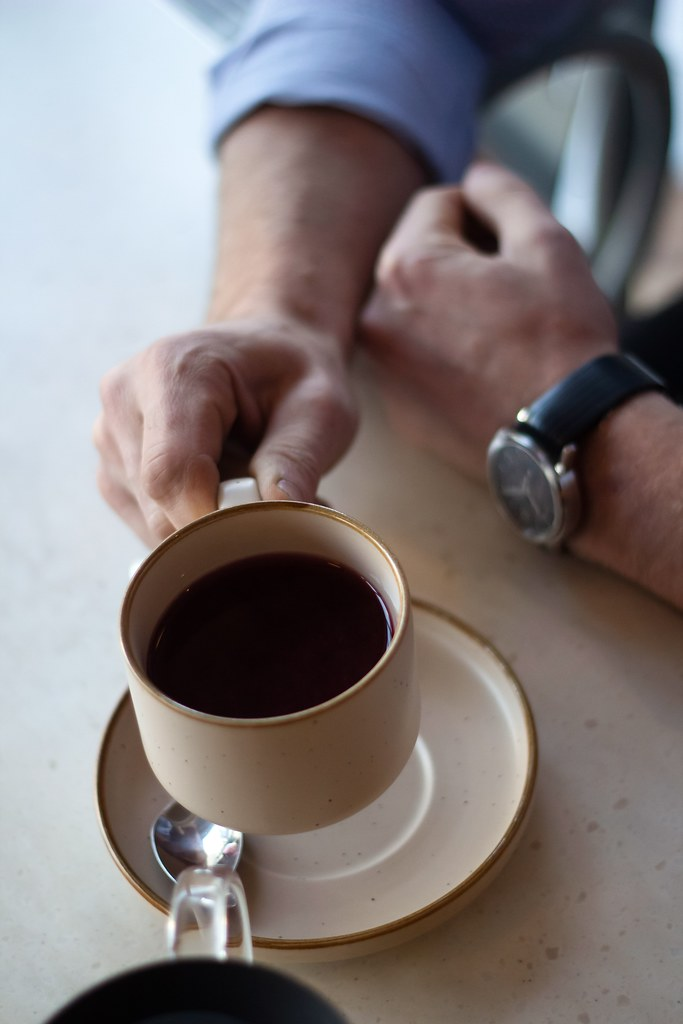 Man holding a cup of black coffee