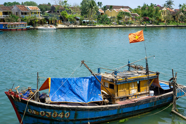 Wooden Fishing Boat with Rain Cover and Vietnamese Flag on a River with Houses and Palm Trees in the Background in Hoi An, Vietnam