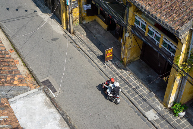 Bird View Photo from a Rooftop Cafe of a Motorbike driving through the empty Old Town of Hoi An, Vietnam