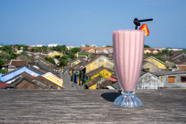 Ice Blended Strawberry Smoothie in a Milkshake Glass with Plastic Drinking Straw and Slice of Fresh Strawberry on a Rooftop overlooking the Old Town of Hoi An, Vietnam