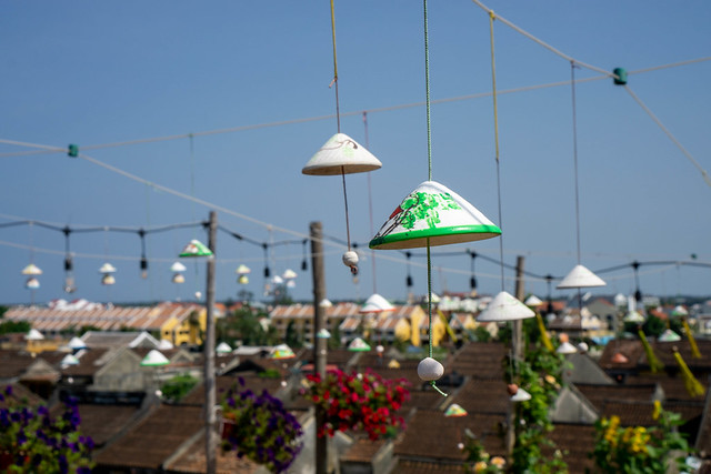 Close Up View of Small Hanging Miniature Vietnamese Conical Hat in Flower Design on a Rooftop Restaurant and Cafe with Houses in the Background in Hoi An, Vietnam