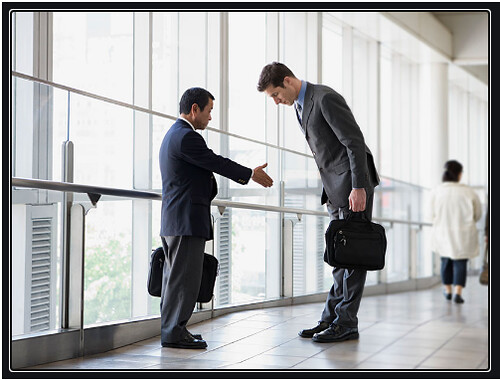 Doing Business in China? 19 Cultural Differences You Should Know. Image is of 2 business people shaking hands or bowing in a glass-enclosed hallway
