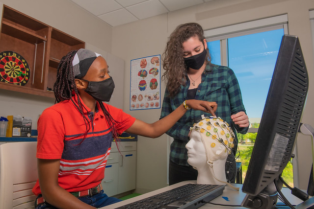 Joyce Kimeli and Juliana Otoni Parma look at a piece of kinesiology equipment in a lab.